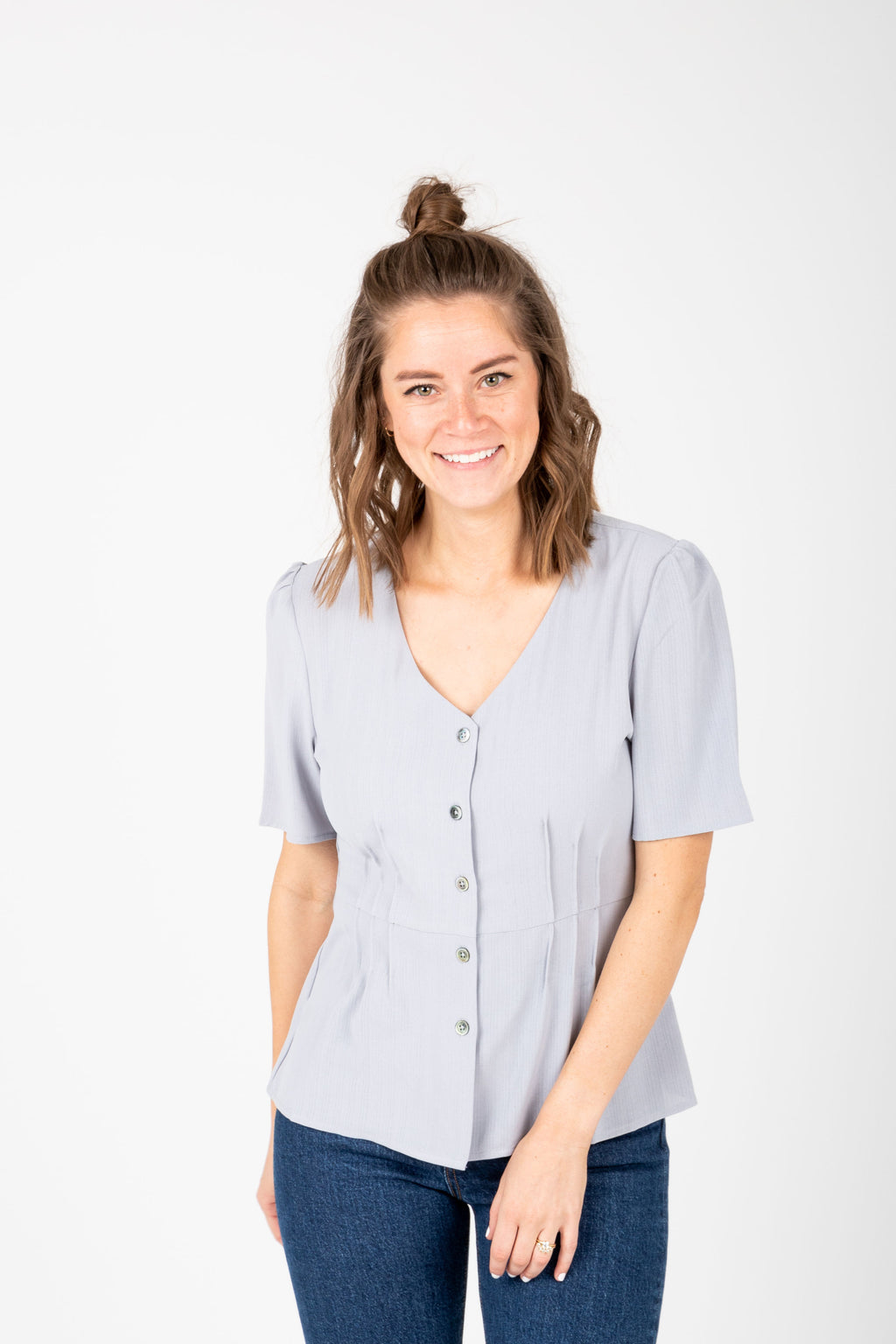 The Taliyah Pleated Peplum Blouse in Grey, studio shoot; front view
