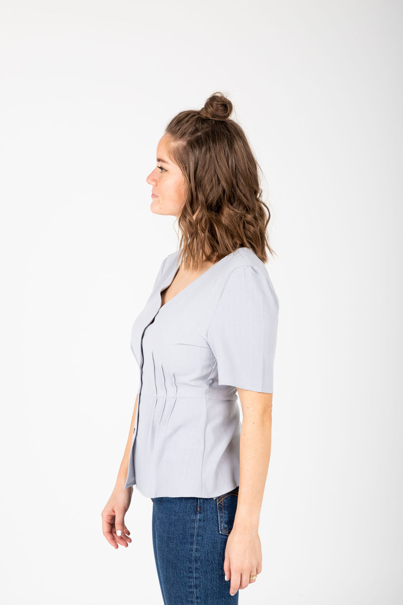 The Taliyah Pleated Peplum Blouse in Grey, studio shoot; side view