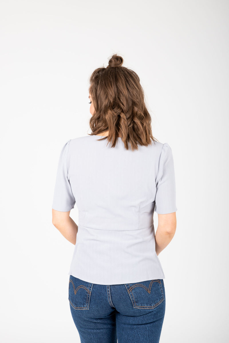 The Taliyah Pleated Peplum Blouse in Grey, studio shoot; back view