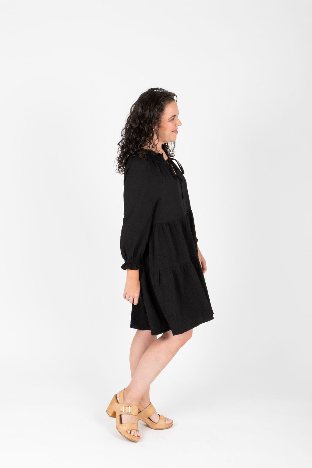The Walsh Tiered Mini Dress in Black, studio shoot; side view