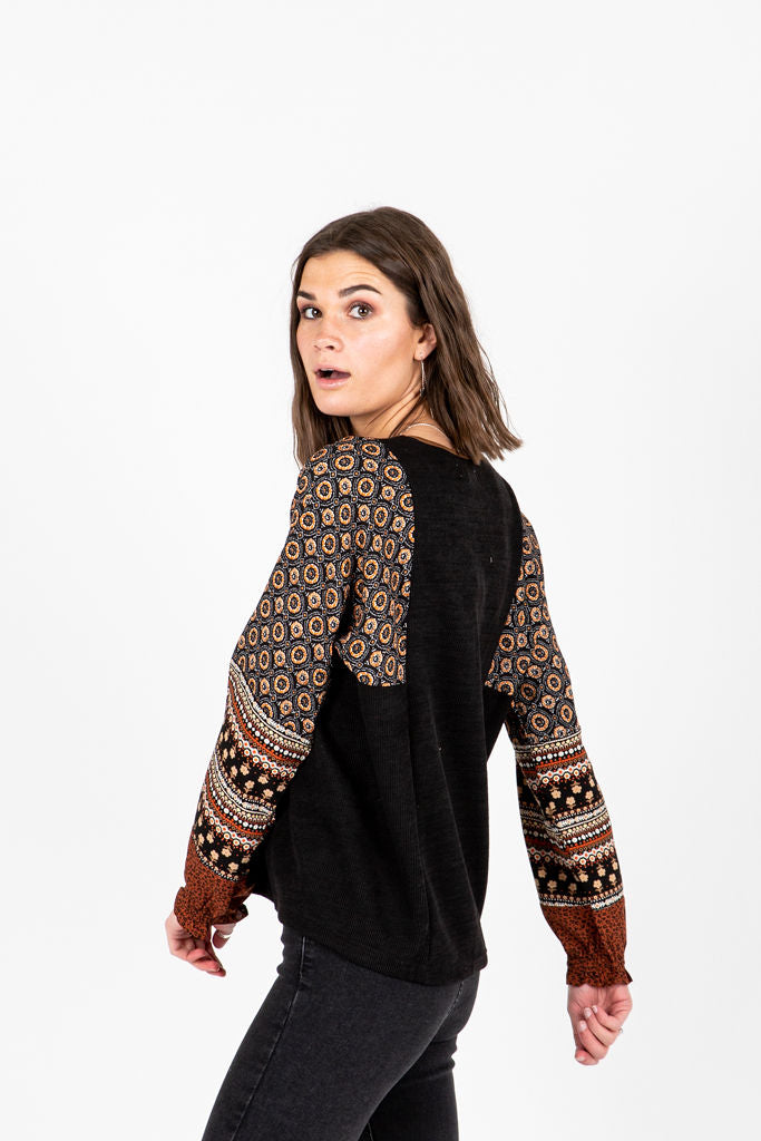 The Eliza Patterned V-Neck Blouse in Black, studio shoot; side view