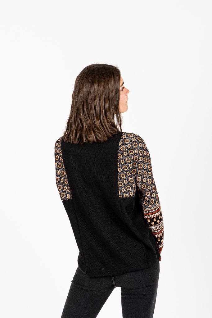 The Eliza Patterned V-Neck Blouse in Black, studio shoot; back view