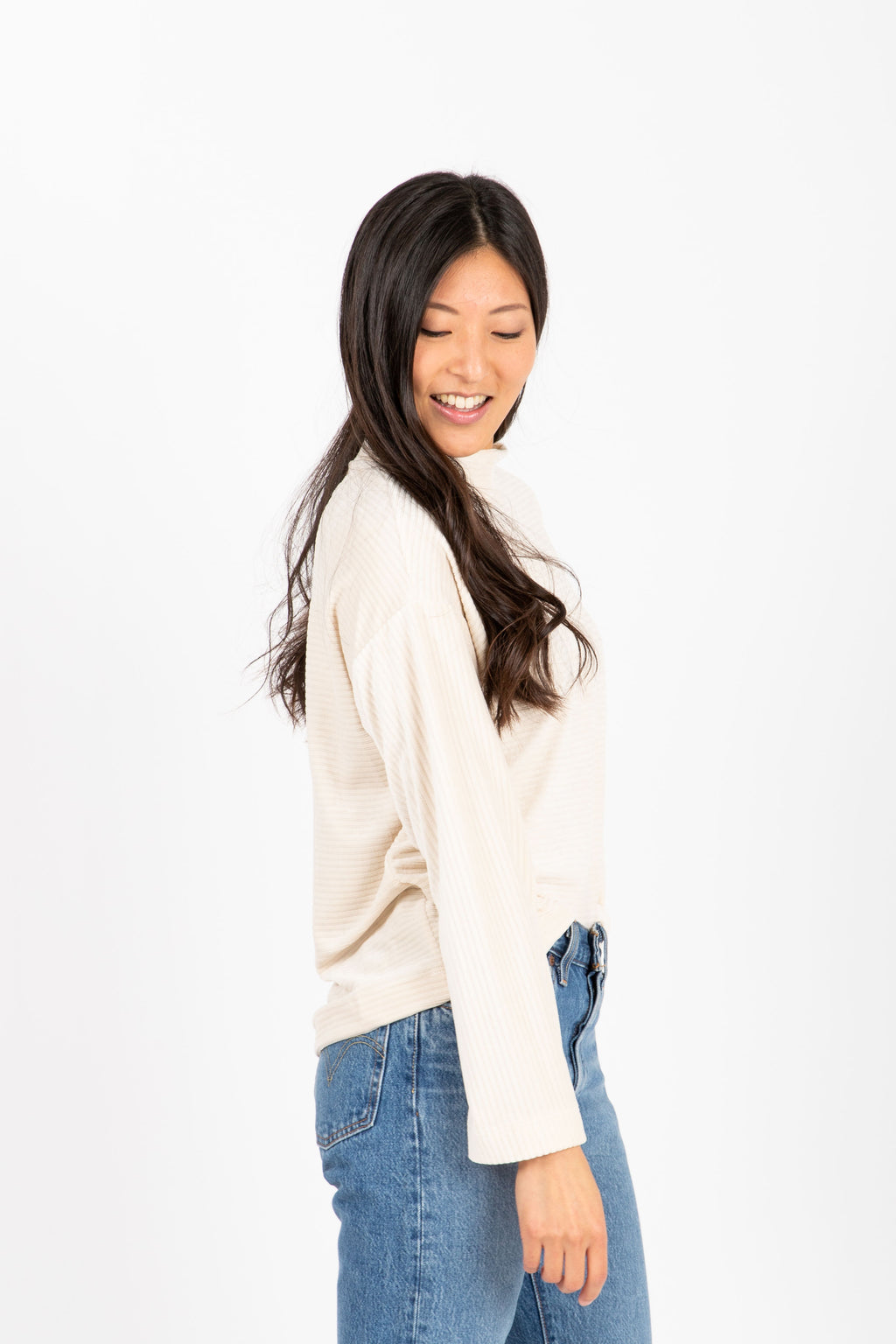The Virgina Ribbed Mock Neck Sweater in Cream, studio shoot; side view
