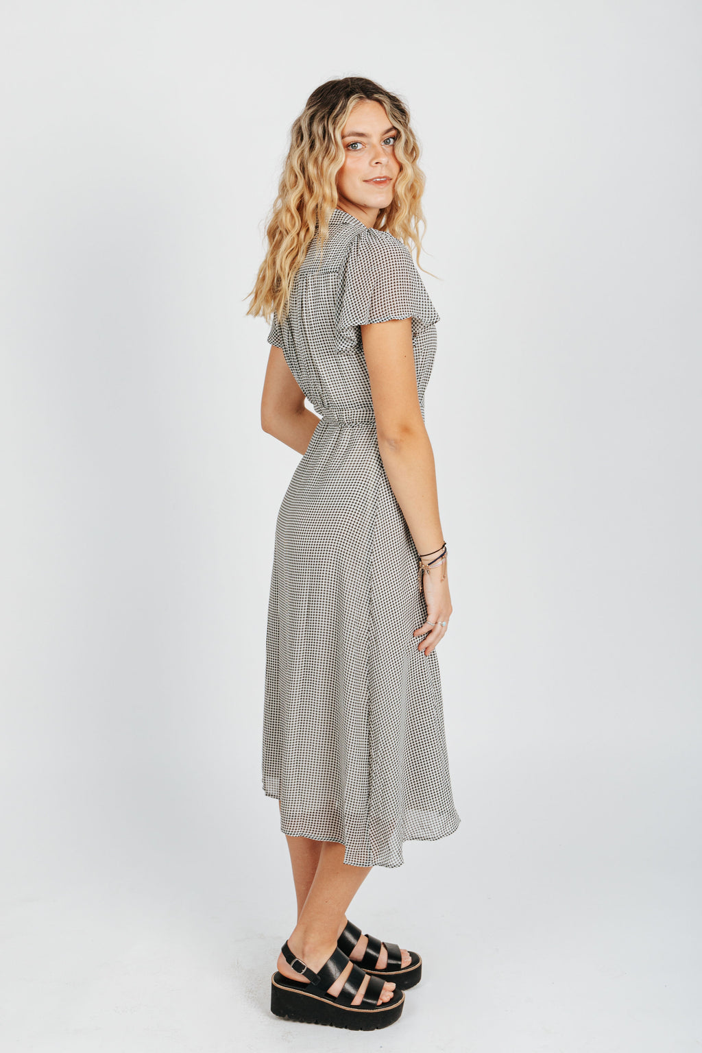 The Benfield Gingham Wrap Dress in Black, studio shoot; side view