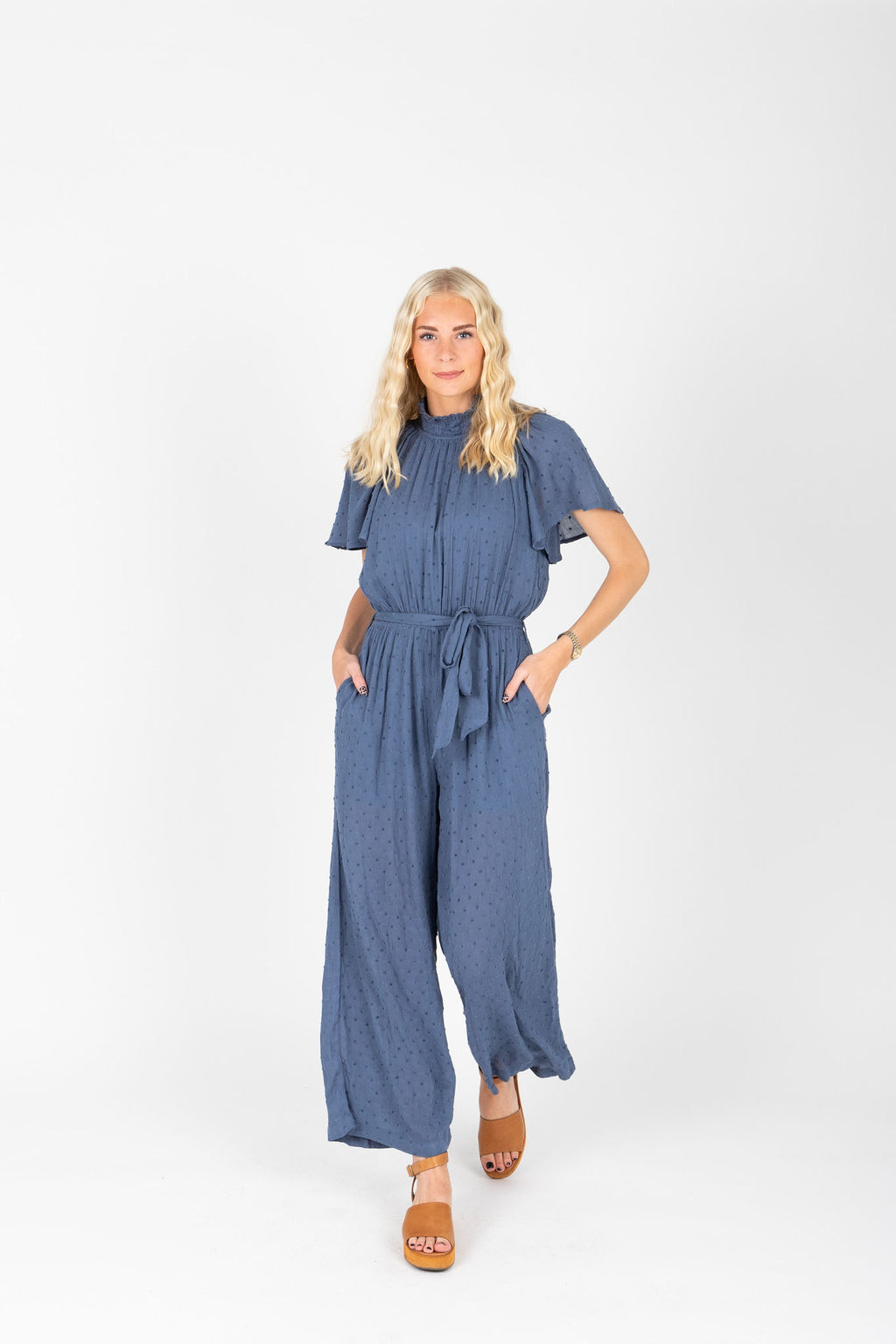 The Grier Swiss Dot Ruffle Jumpsuit in Dusty Blue, studio shoot; front view