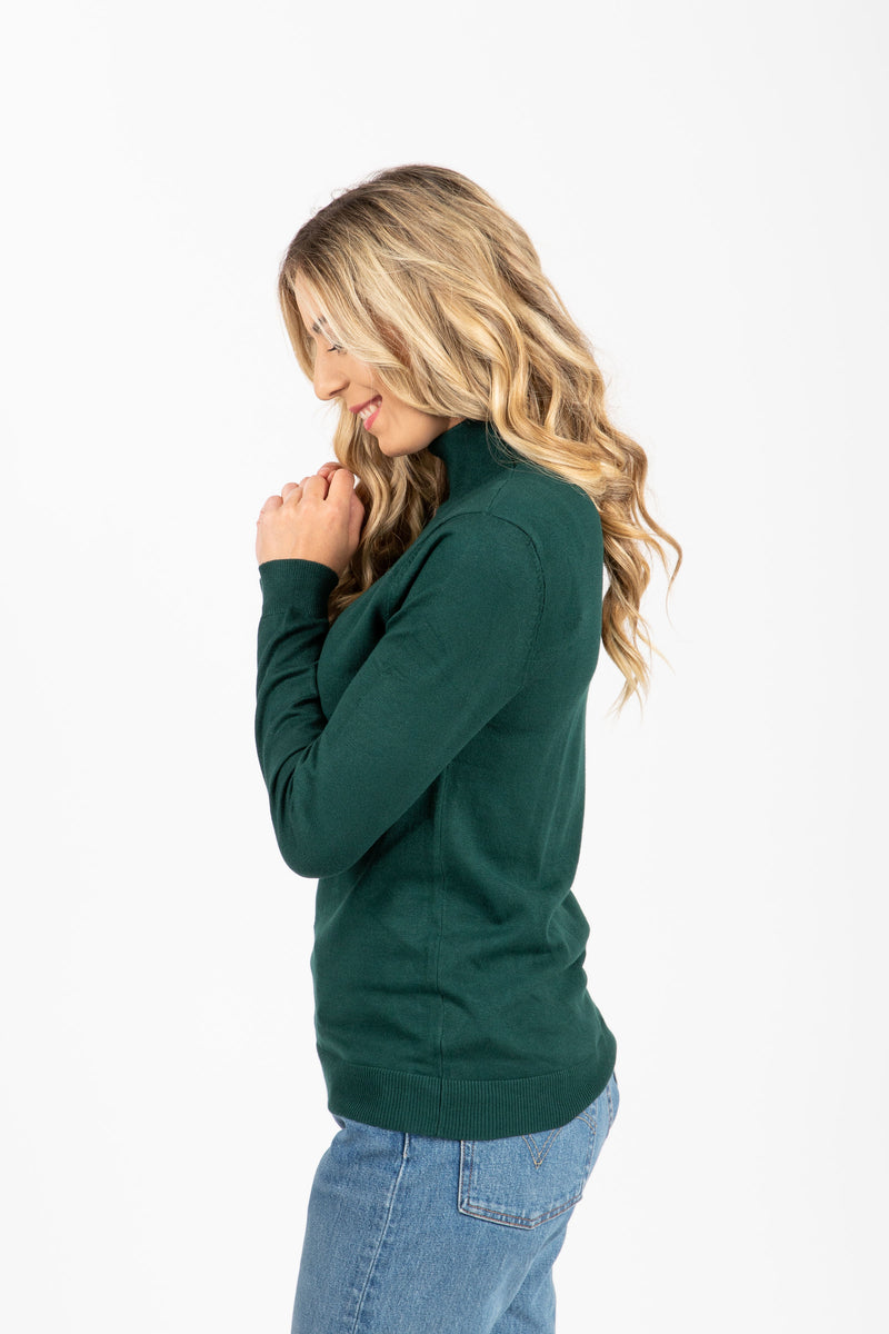 The Tate Turtleneck Sweater in Hunter Green, studio shoot; side view