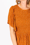 The Veruca Smocked Tiered Dress in Camel, studio shoot; closer up front view