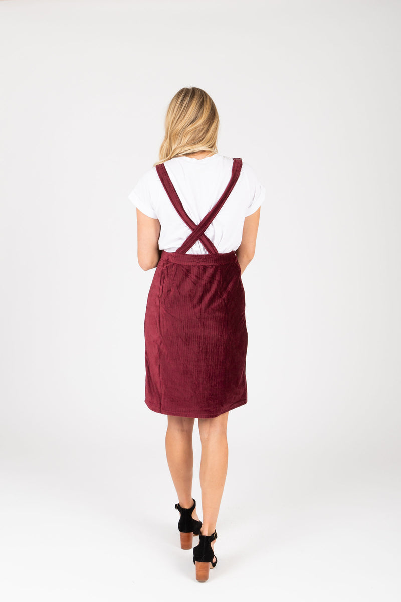 The Dottin Corduroy Jumper Dress in Burgundy, studio shoot; back view