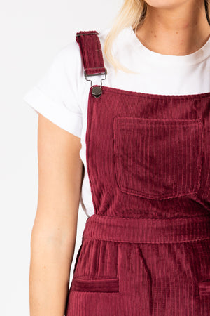 The Dottin Corduroy Jumper Dress in Burgundy, studio shoot; closer up front view