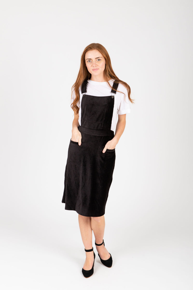 The Dottin Corduroy Jumper Dress in Black, studio shoot; front view