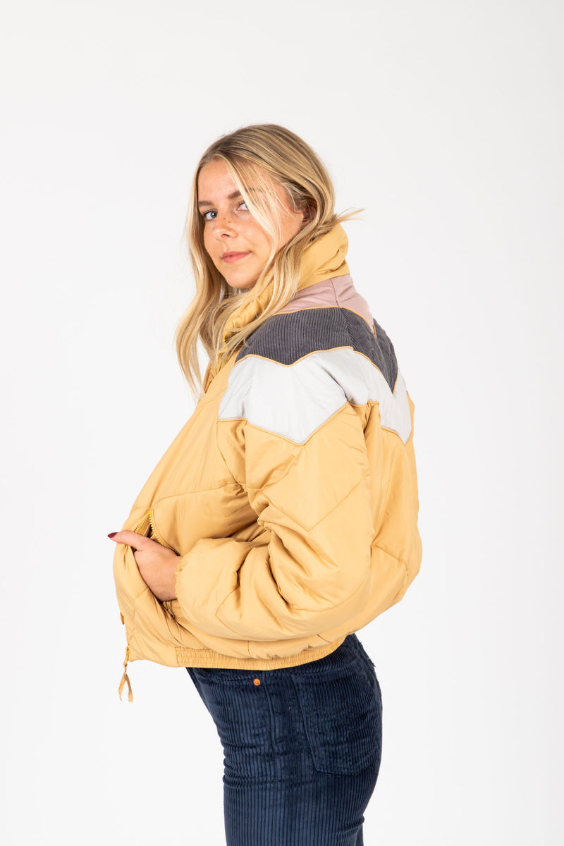 The Babita Padded Bomber Jacket in Mustard, studio shoot; side view