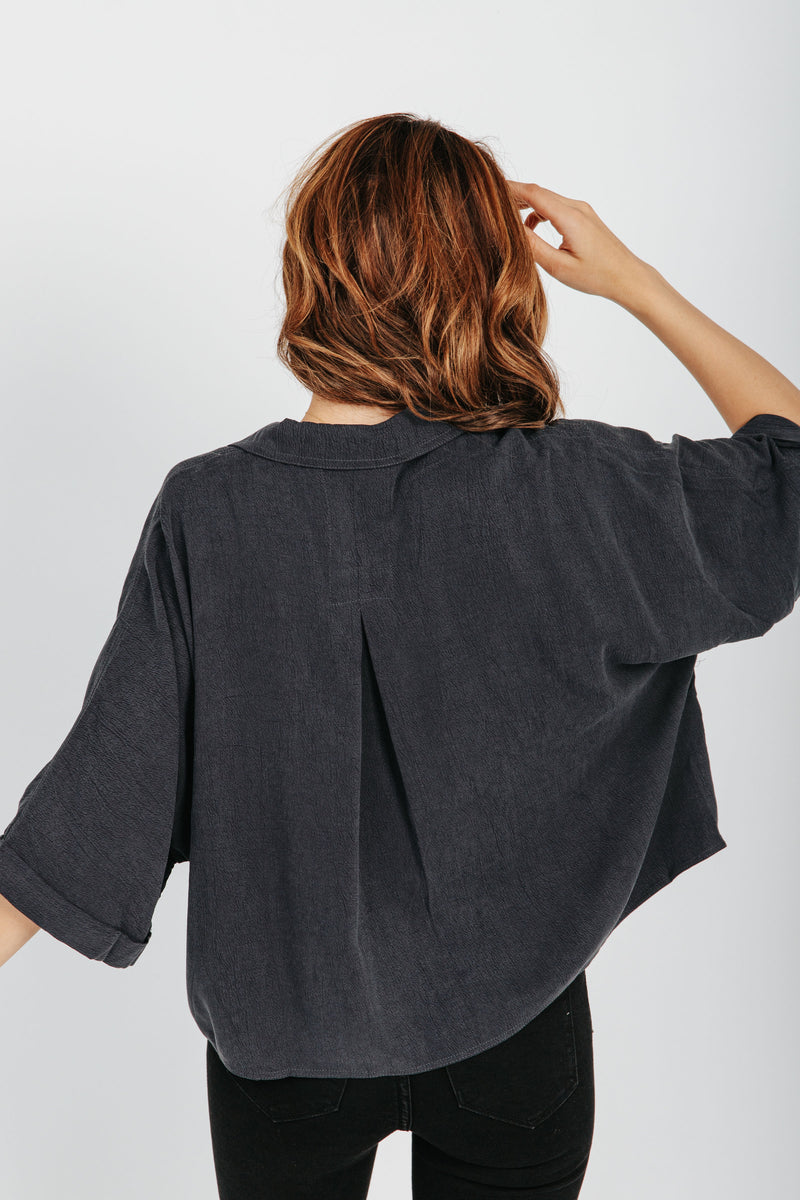 The Camryn Pocket Blouse in Charcoal, studio shoot; back view