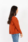 The Saylor Ribbed Button Sweater in Brick, studio shoot; side view