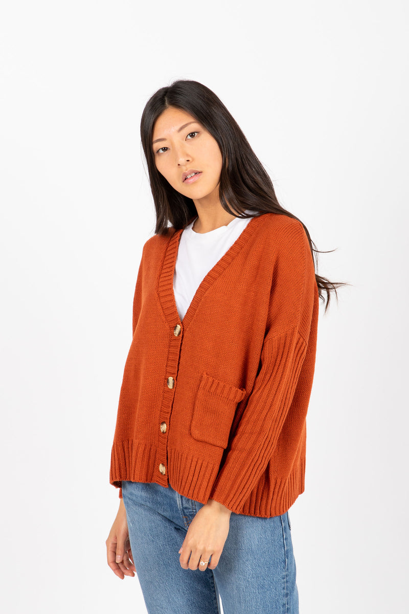 The Saylor Ribbed Button Sweater in Brick, studio shoot; front view