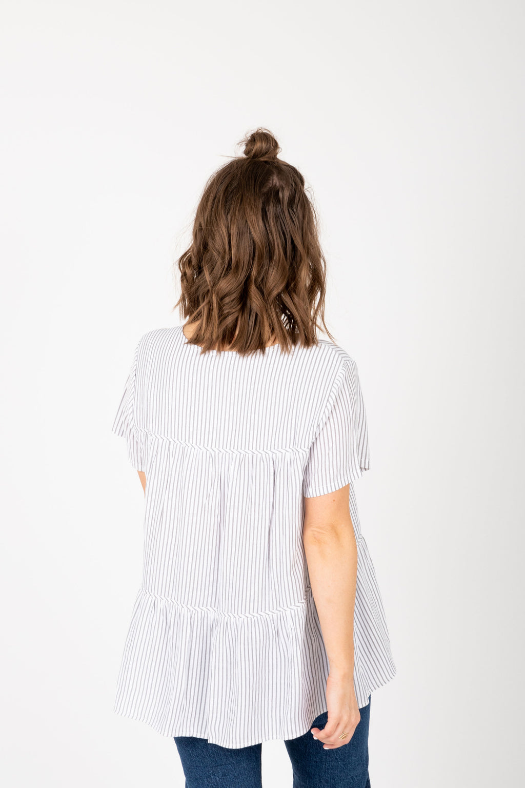 The Austyn Striped Tiered Peplum Blouse in Grey, studio shoot; back view