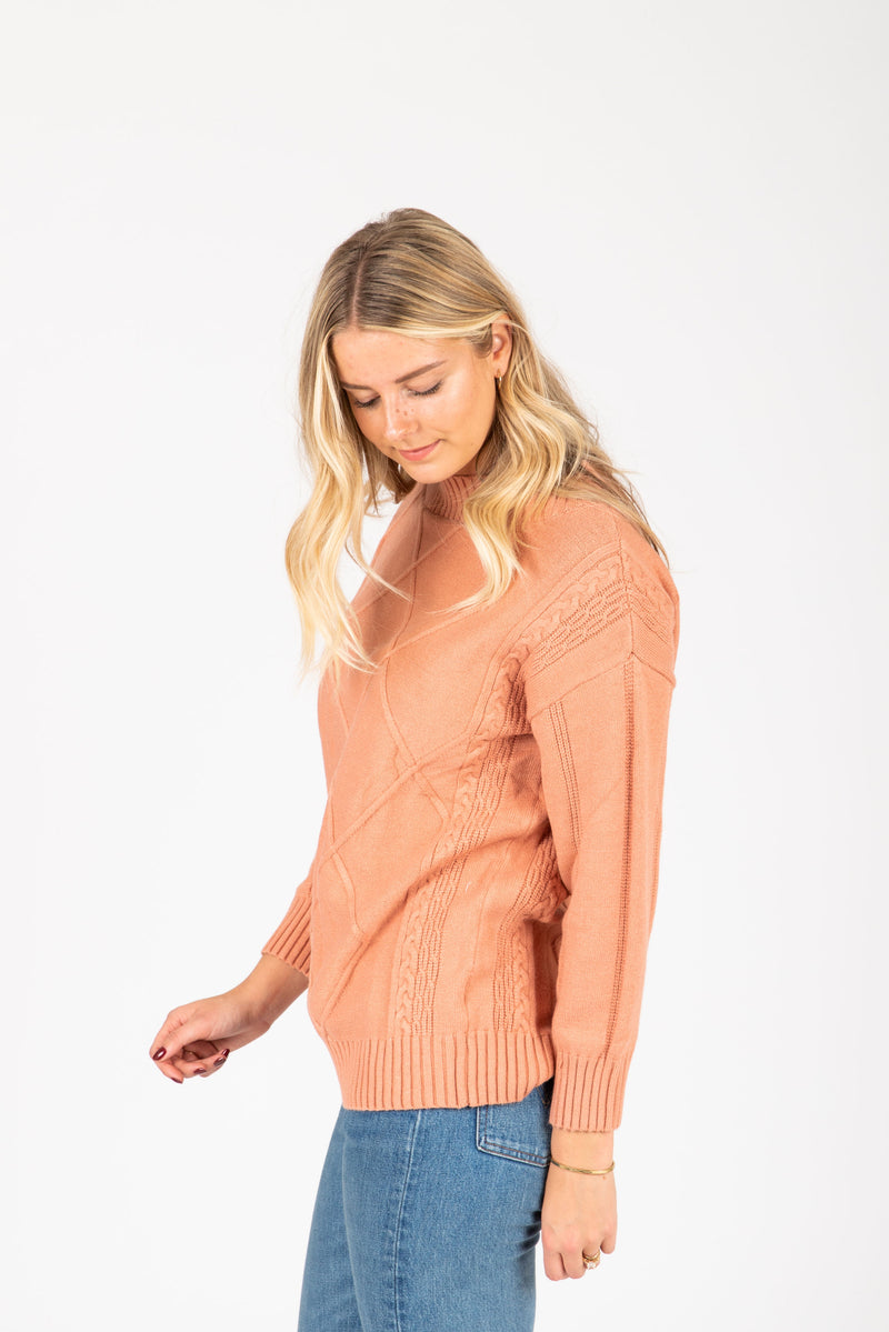 The Gertrude Diamond Sweater in Peach, studio shoot; side view