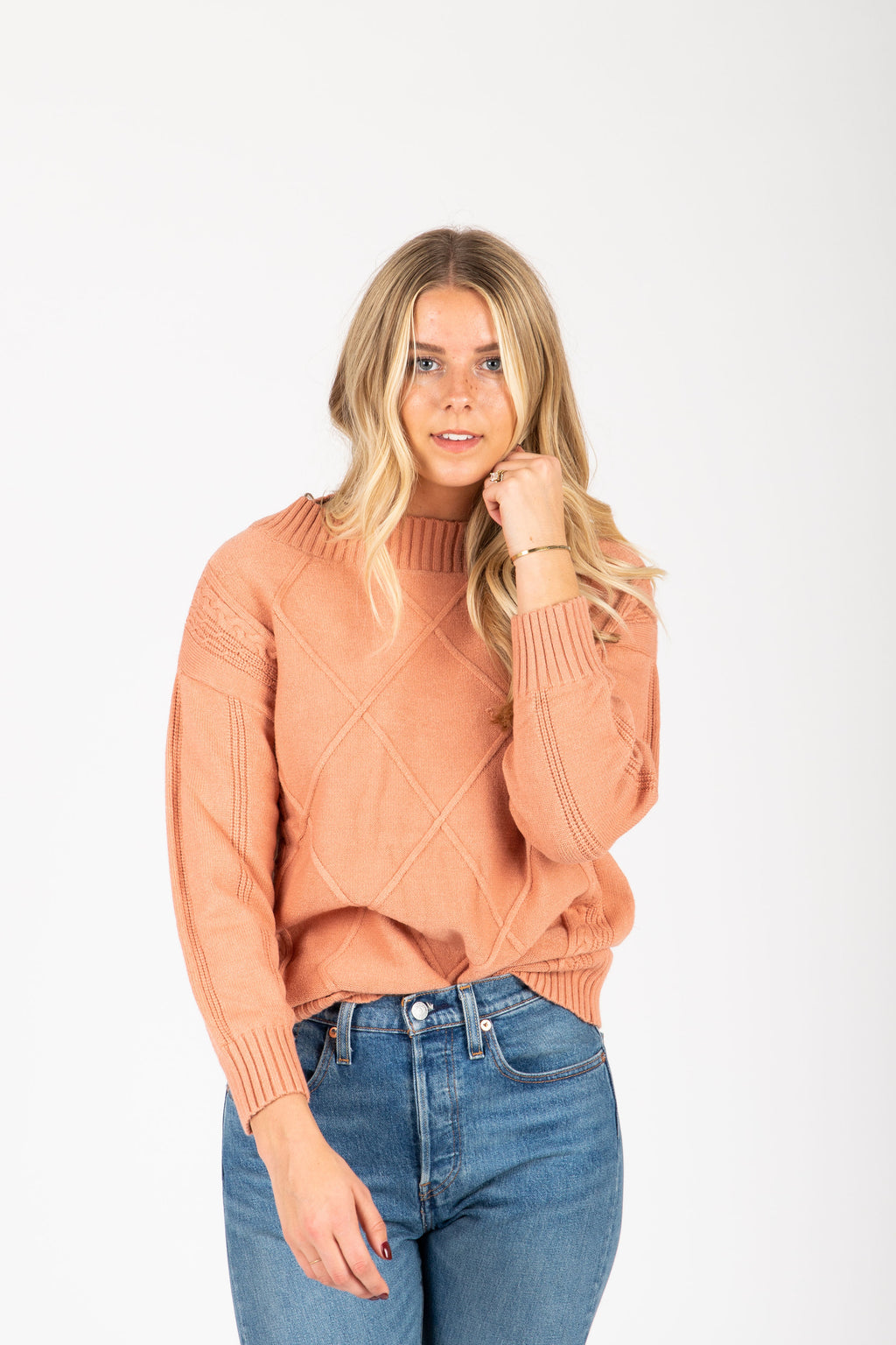 The Gertrude Diamond Sweater in Peach, studio shoot; front view