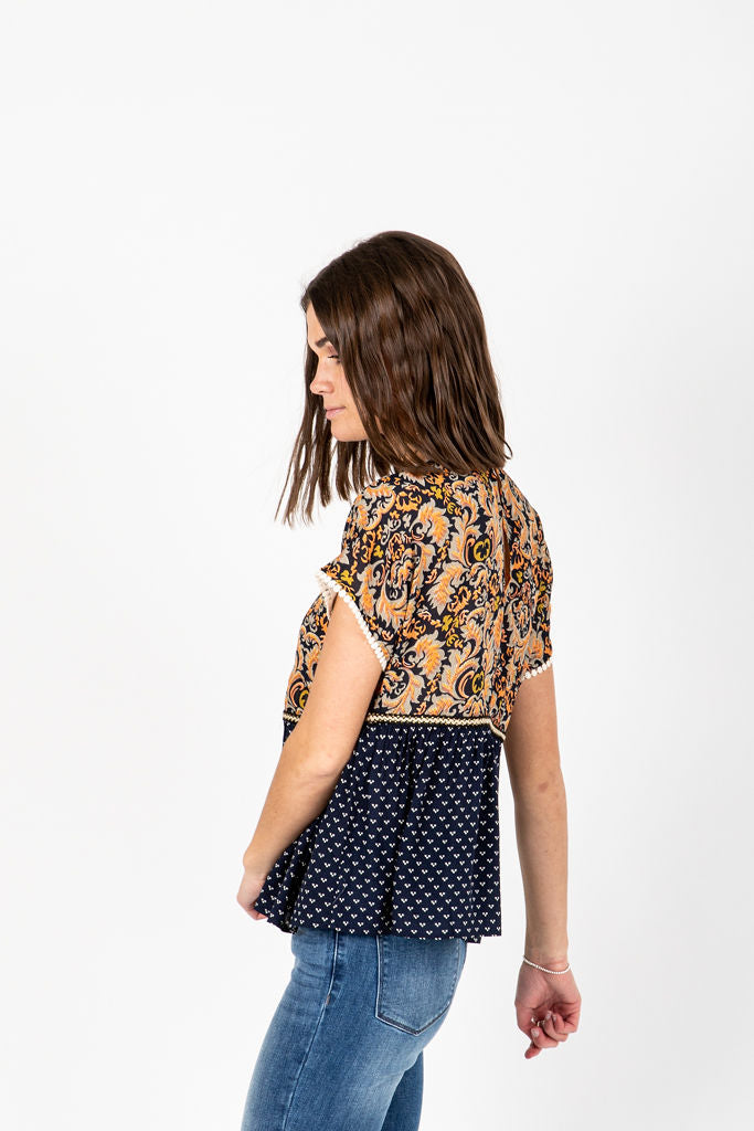 The Braff Pom Detail Blouse in Navy, studio shoot; side view