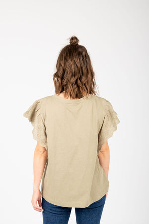 The Elina Eyelet Ruffle Blouse in Faded Olive, studio shoot; back view