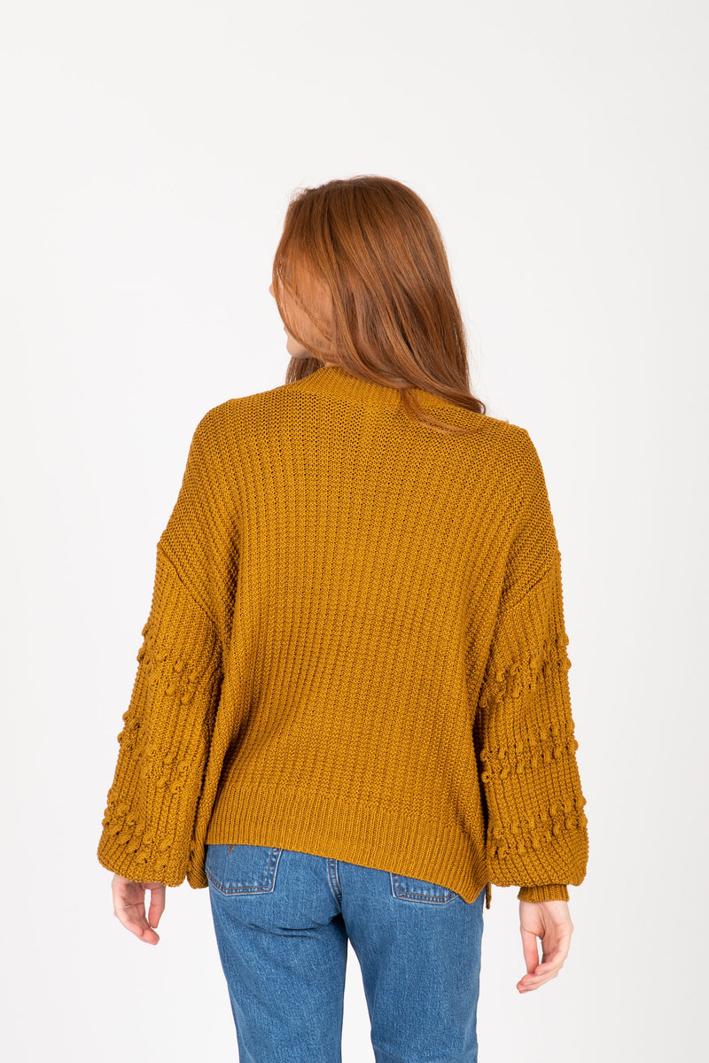 The Clarise Open Pocket Cardigan in Mustard, studio shoot; back view