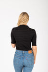 The Nicholls Ruffle Trim Mock Neck in Black, studio shoot; back view