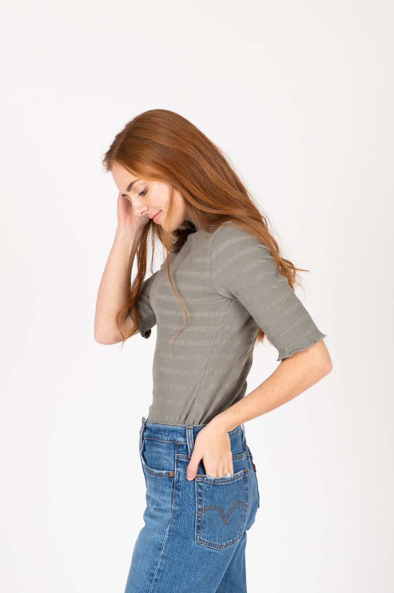 The Nicholls Ruffle Trim Mock Neck in Faded Olive, studio shoot; side view