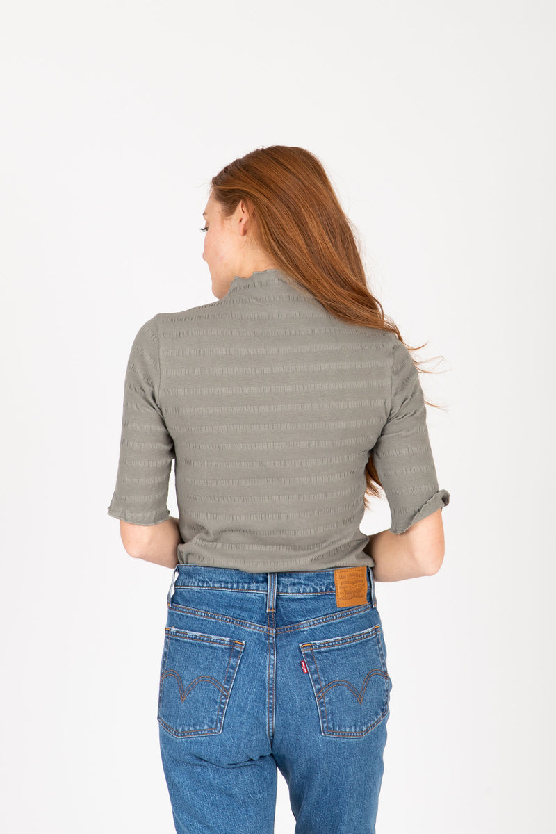 The Nicholls Ruffle Trim Mock Neck in Faded Olive, studio shoot; back view