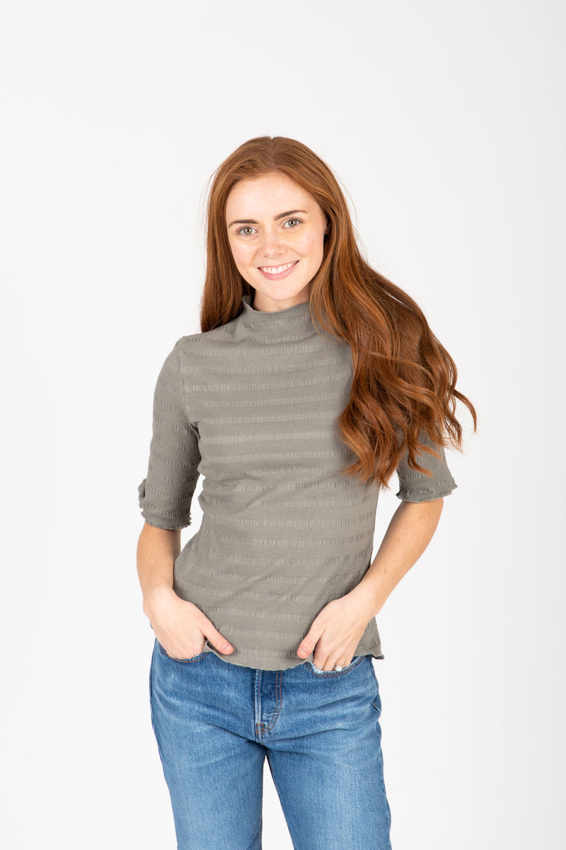 The Nicholls Ruffle Trim Mock Neck in Faded Olive, studio shoot; front view
