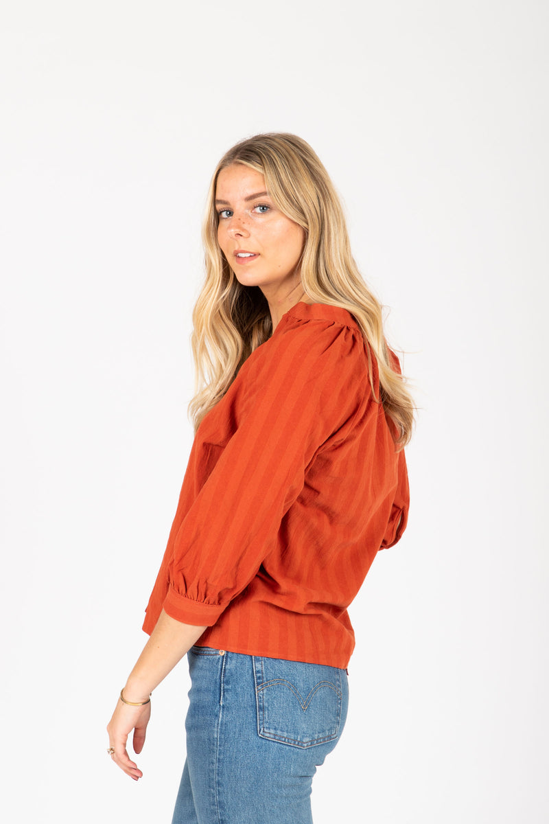 The Stuart Button Blouse in Brick, studio shoot; side view