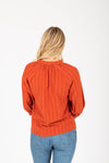 The Stuart Button Blouse in Brick, studio shoot; back view