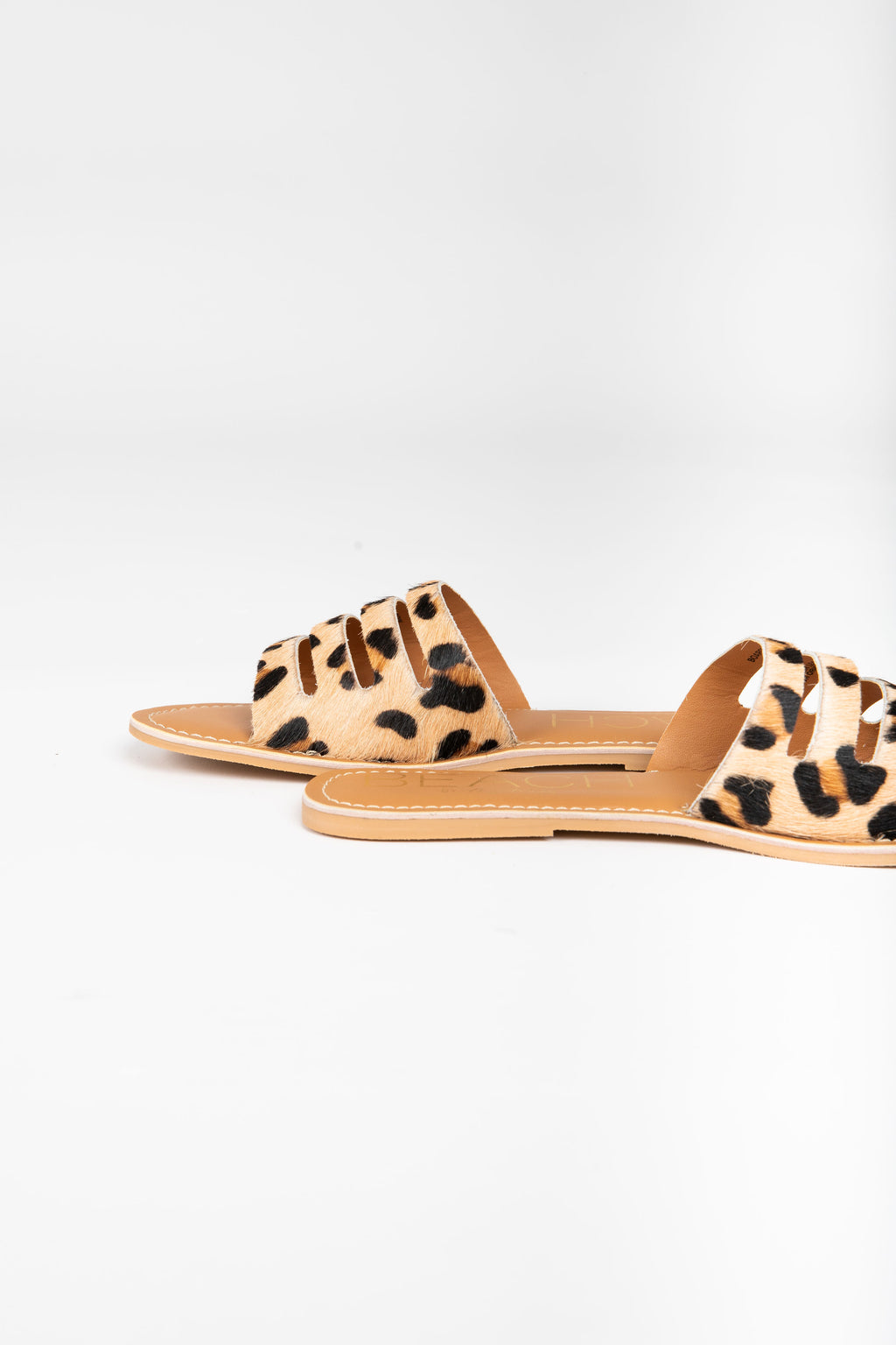 Coconuts by Matisse: Boardwalk Slide Sandal in Leopard, studio shoot; side view