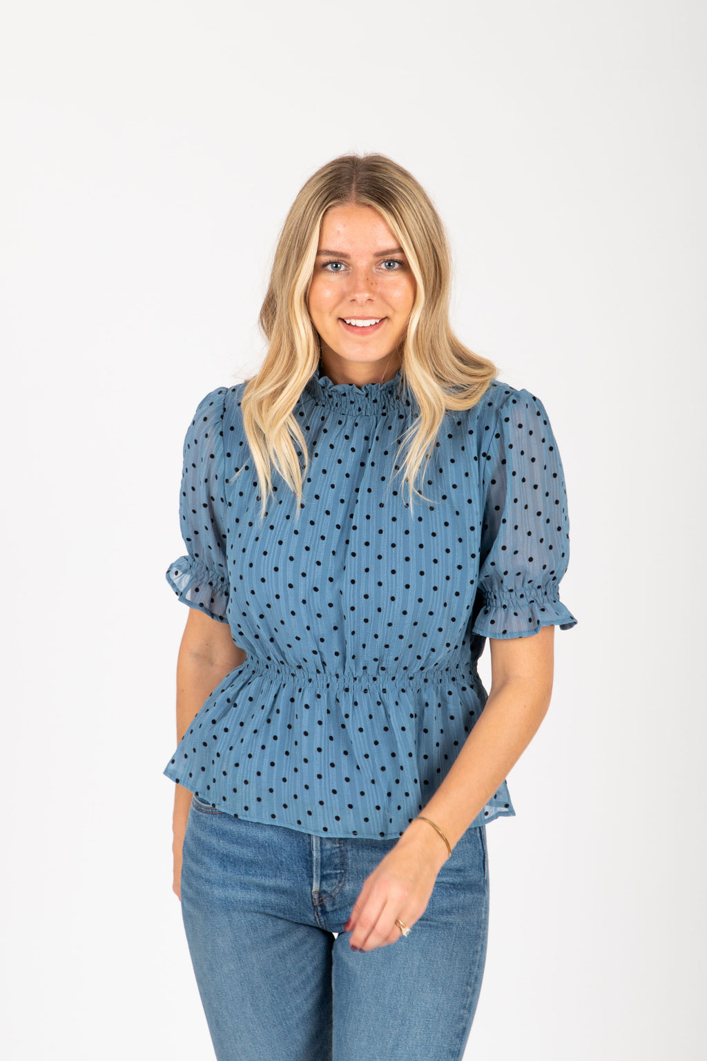 The Perry Dot Peplum Blouse in Blue, studio shoot; front view
