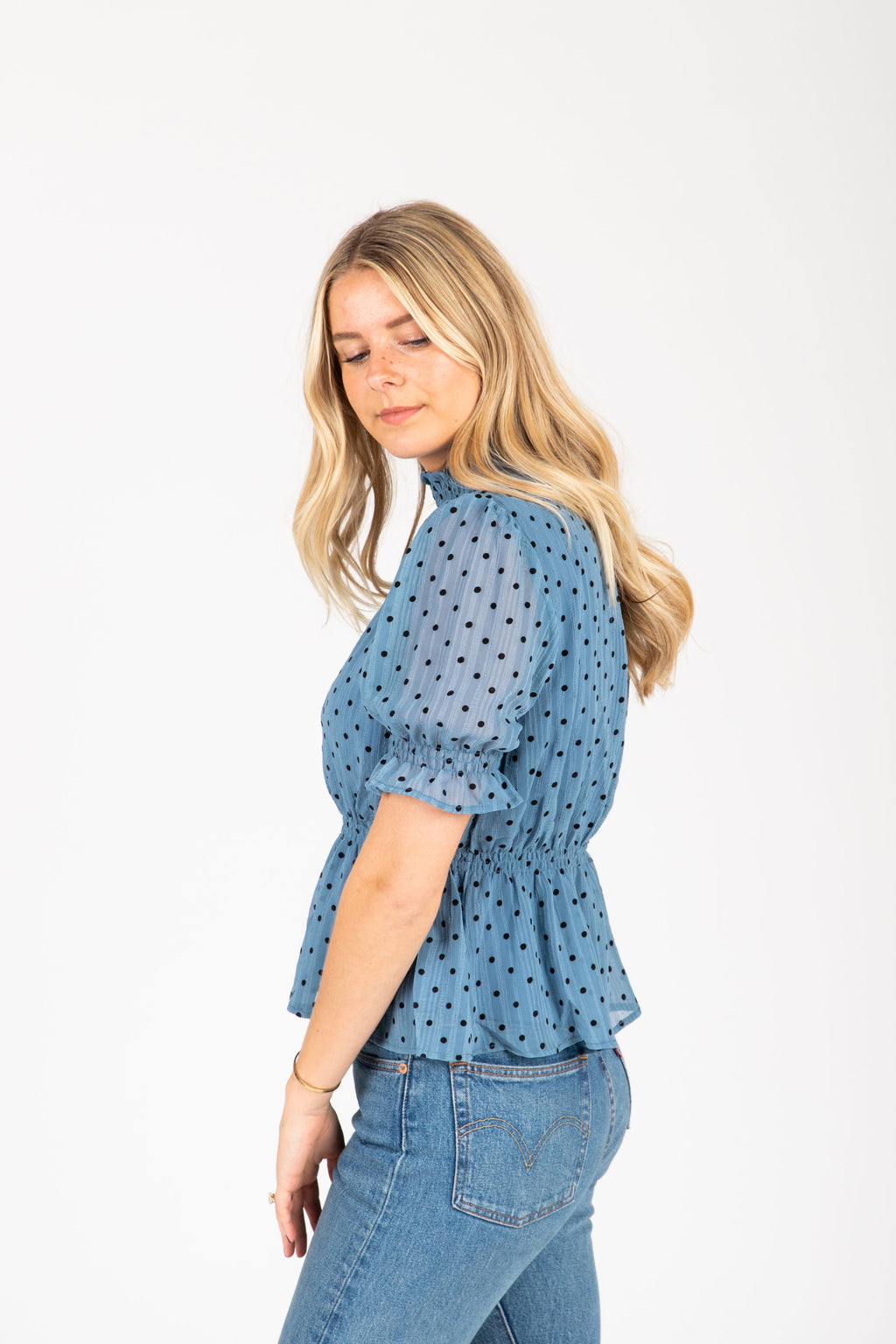 The Perry Dot Peplum Blouse in Blue, studio shoot; side view