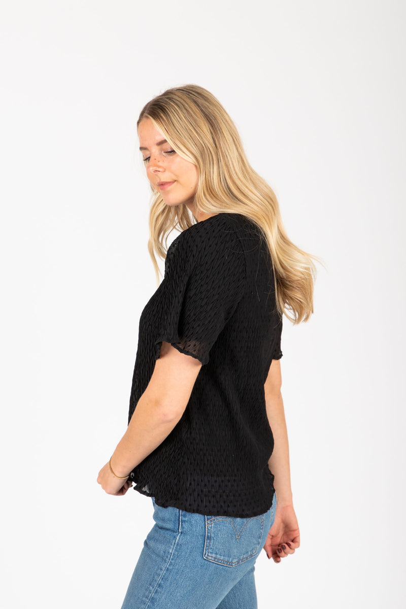The Carlotta Swiss Dot Blouse in Black, studio shoot; side view