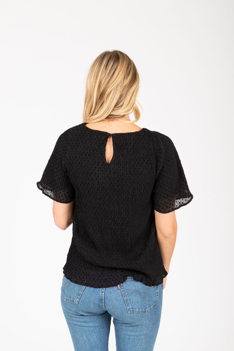 The Carlotta Swiss Dot Blouse in Black, studio shoot; back view