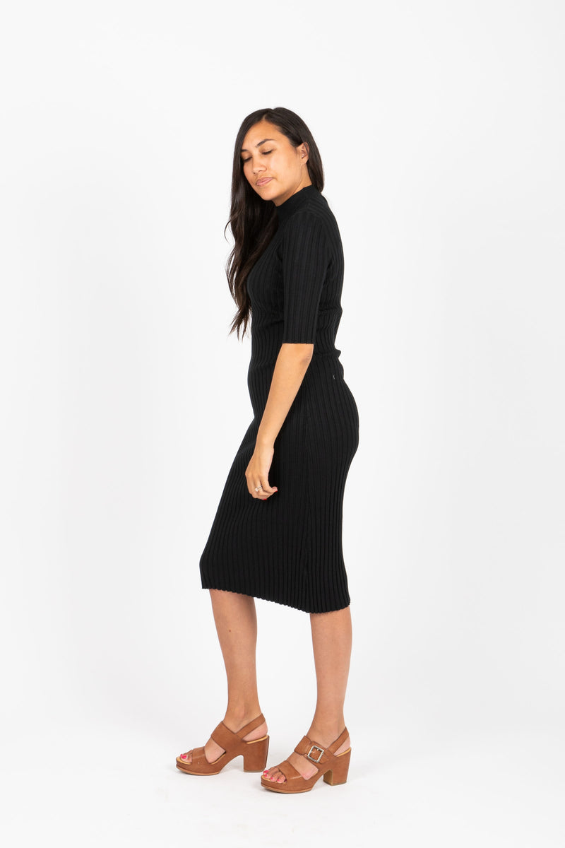 The Eugene Ribbed Sweater Dress in Black, studio shoot; side view