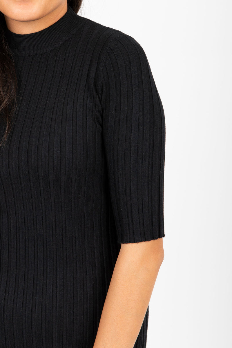 The Eugene Ribbed Sweater Dress in Black, studio shoot; closer up front view