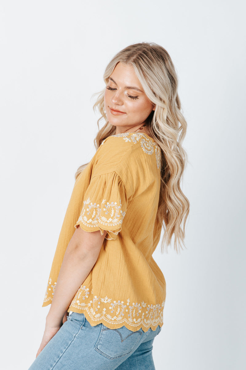 The Harrison Scallop Detail Blouse in Mustard, studio shoot; side view