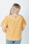 The Harrison Scallop Detail Blouse in Mustard, studio shoot; back view