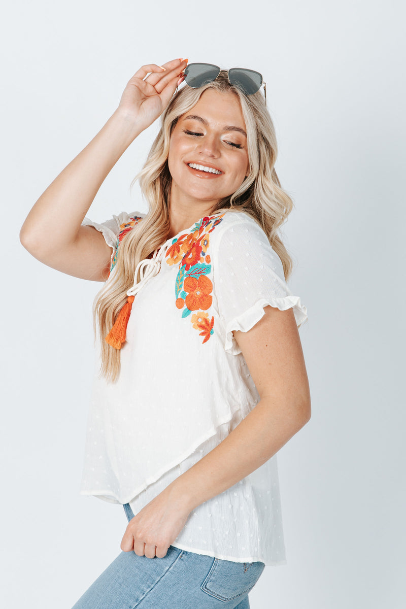 The Audra Embroidered Swiss Dot Blouse in Cream, studio shoot; side view