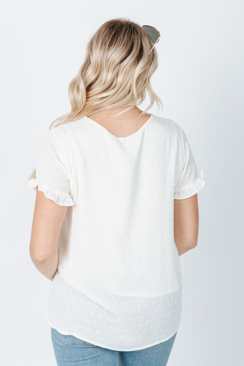 The Audra Embroidered Swiss Dot Blouse in Cream, studio shoot; back view