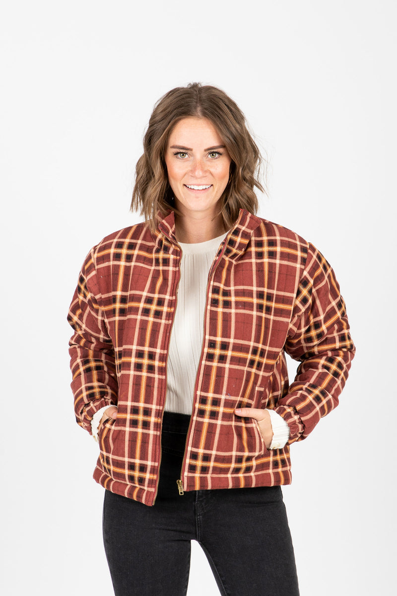 The Baker Plaid Puffer Jacket in Rust, studio shoot; front view