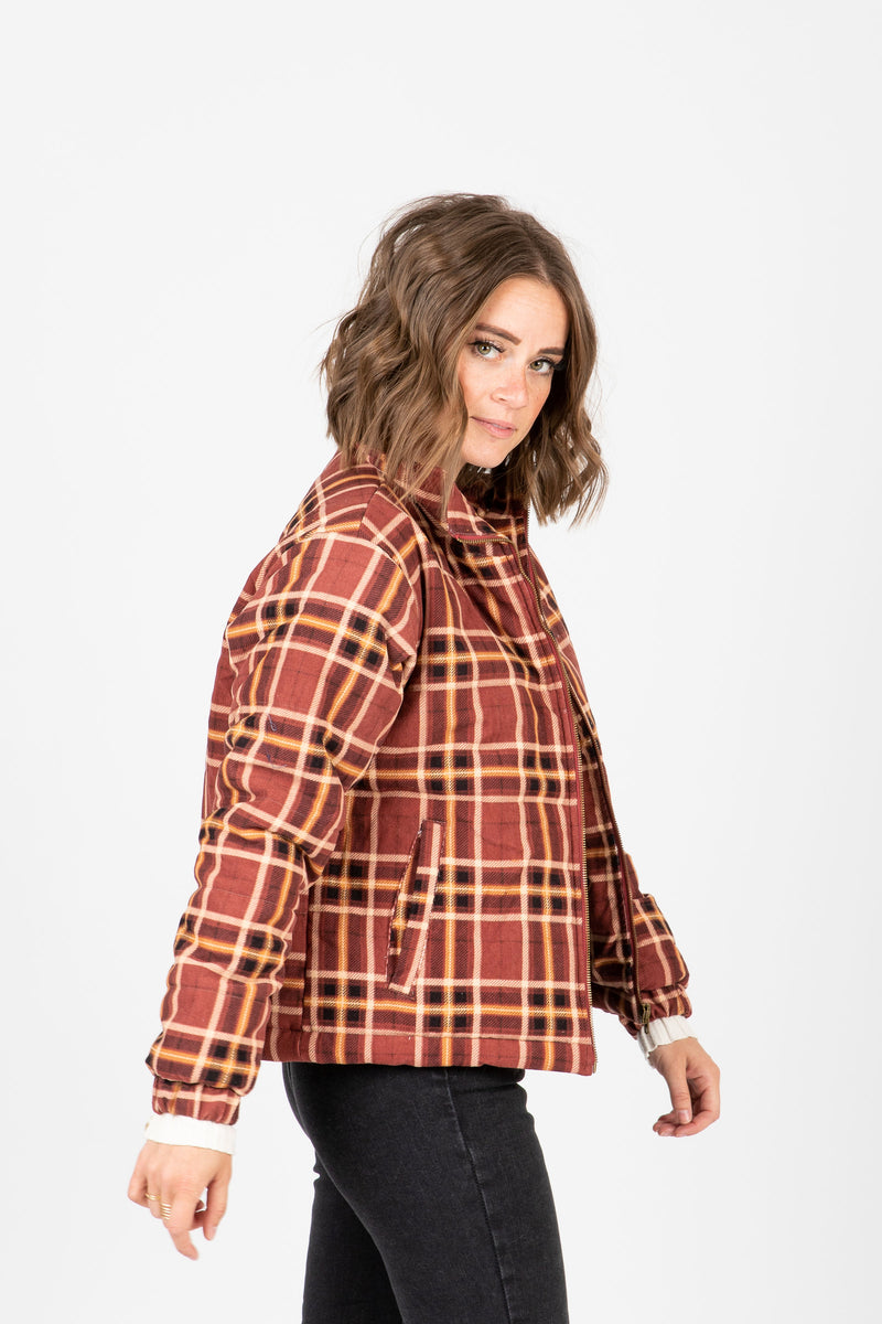 The Baker Plaid Puffer Jacket in Rust, studio shoot; side view