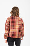 The Baker Plaid Puffer Jacket in Rust, studio shoot; back view