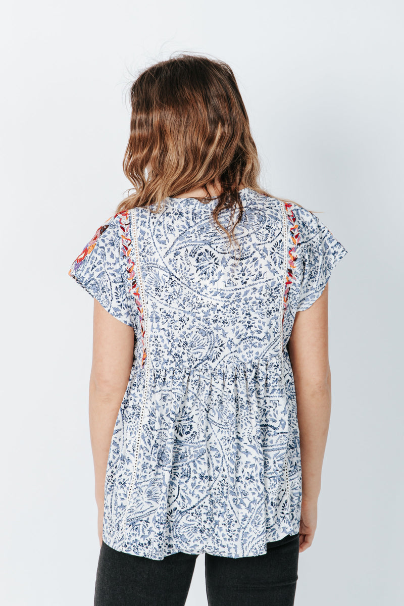 The Griffin Patterned Tassel Blouse in Blue, studio shoot; back view