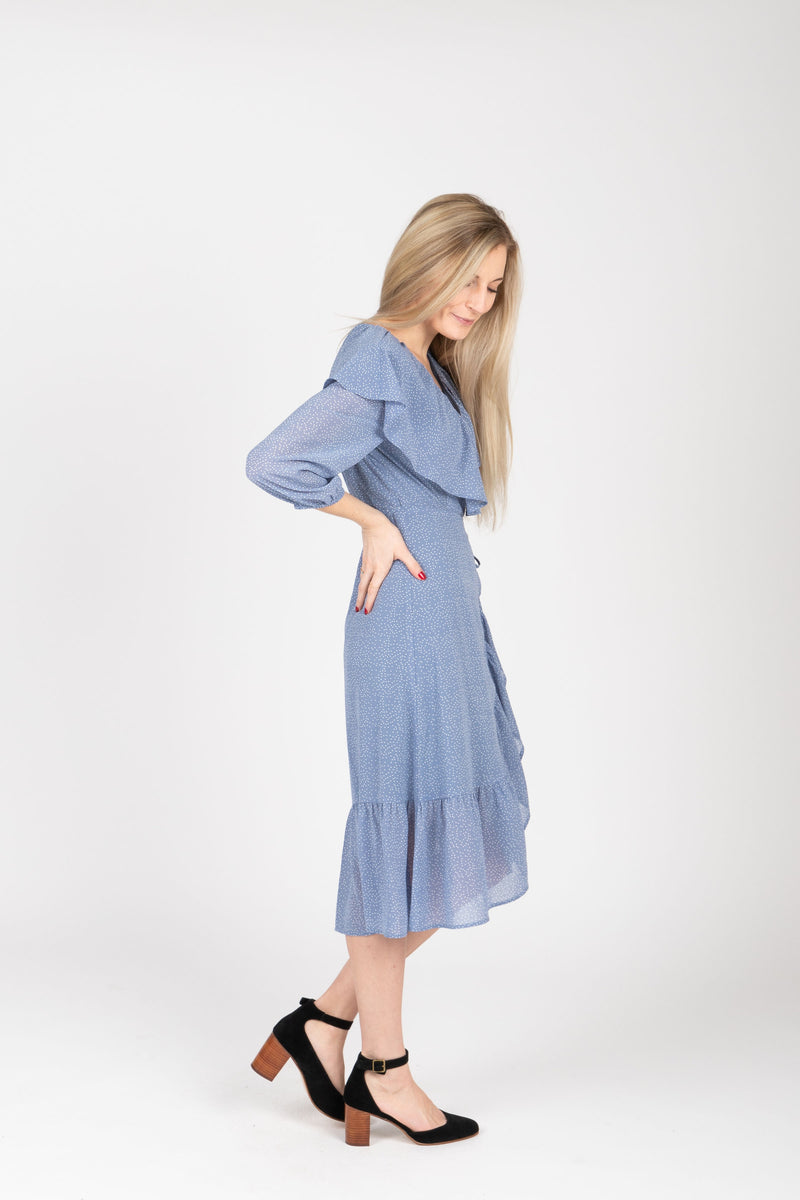 The Vinnie Ruffle Wrap Dress in Powder Blue, studio shoot; side view