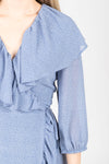 The Vinnie Ruffle Wrap Dress in Powder Blue, studio shoot; closer up front view