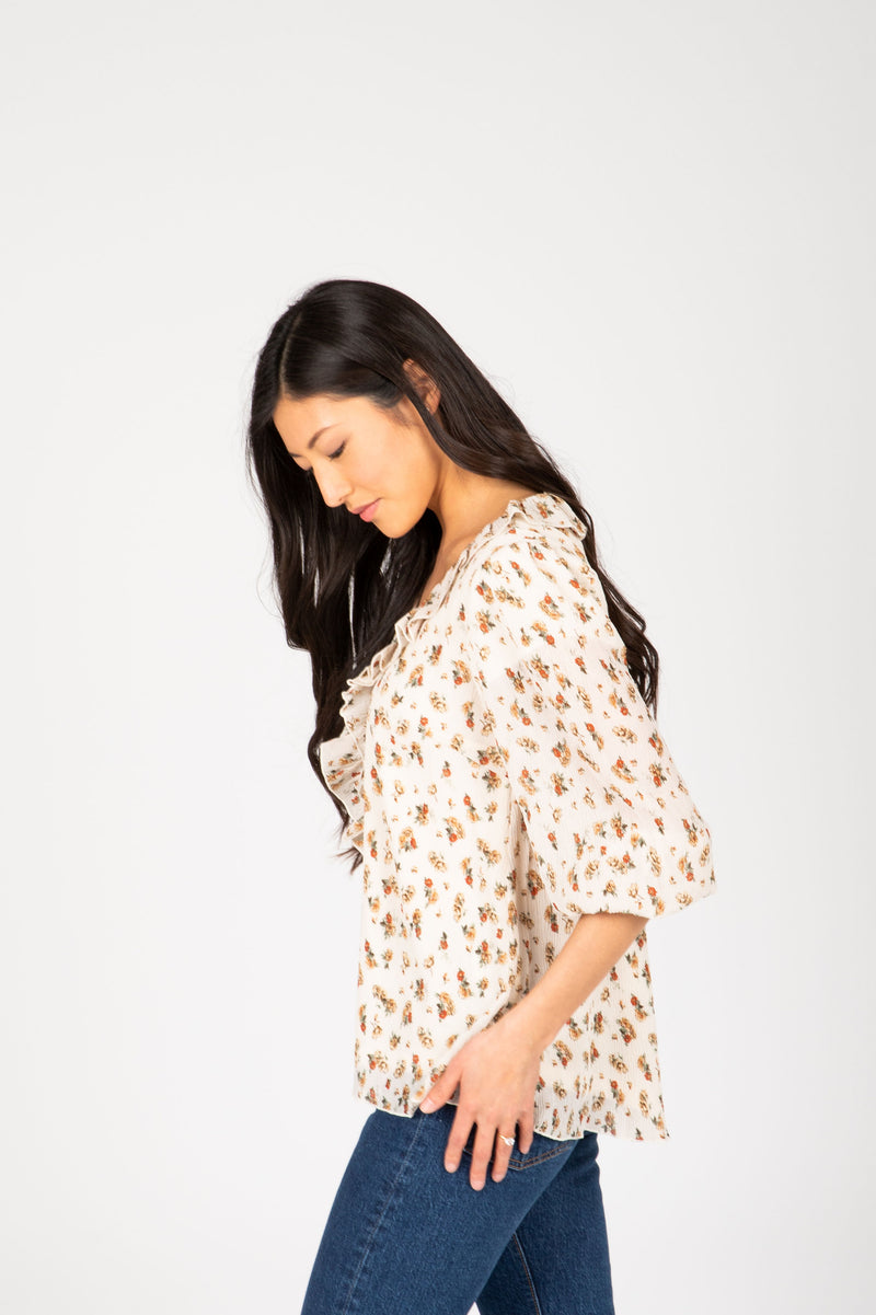 The Etta Floral Ruffle Blouse in Natural, studio shoot; side view