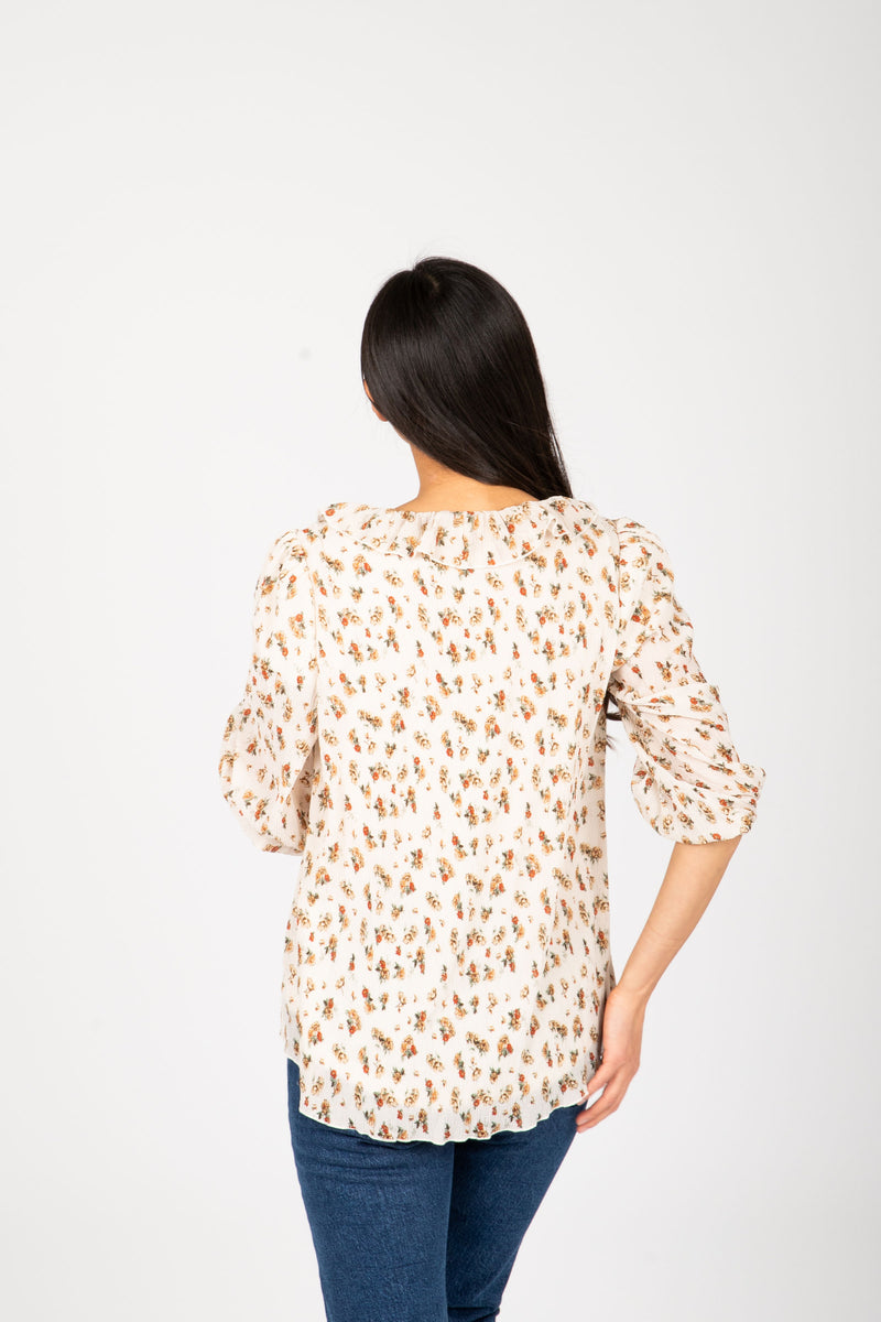 The Etta Floral Ruffle Blouse in Natural, studio shoot; back view