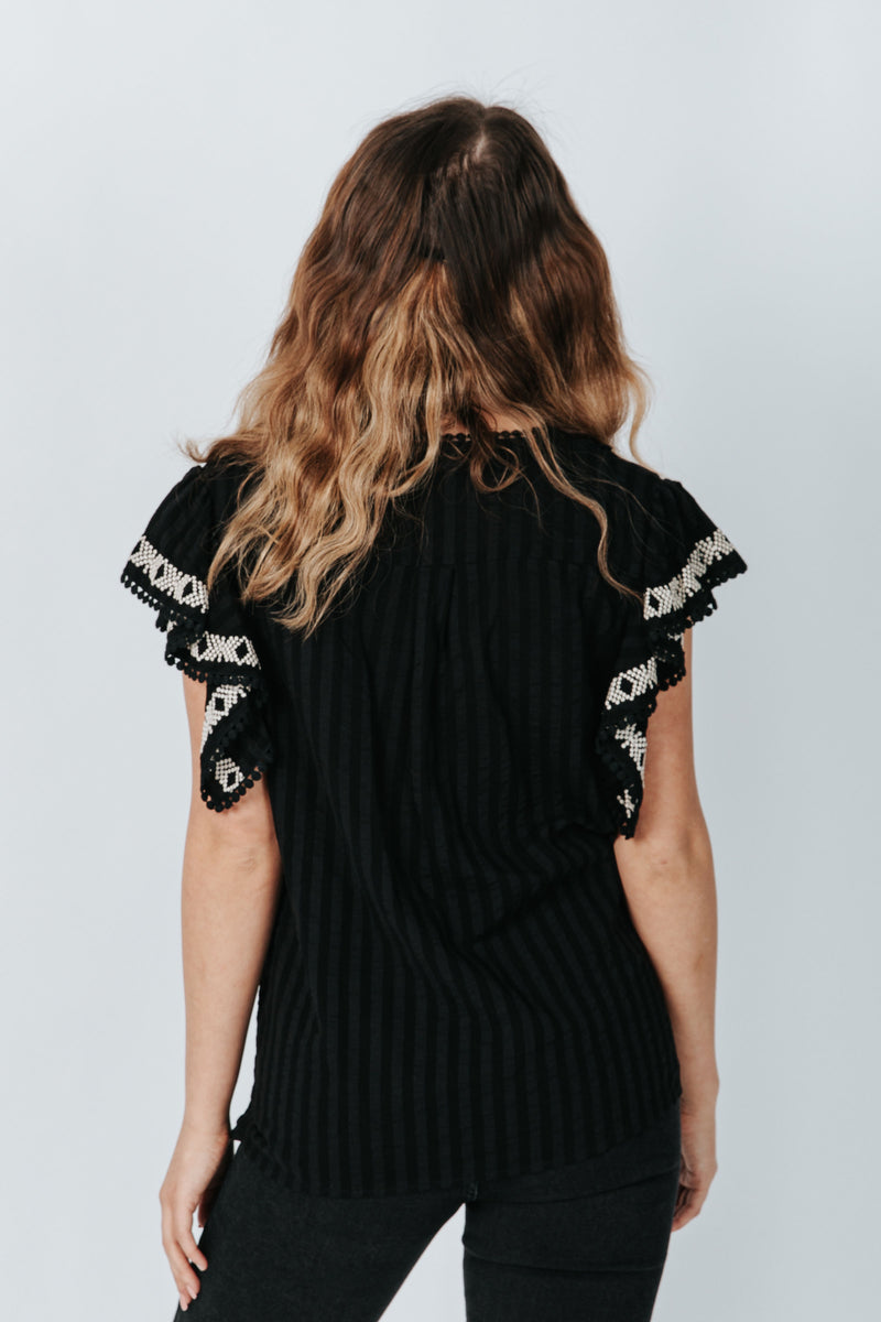The Tara Ruffle Detail Blouse in Black, studio shoot; back view